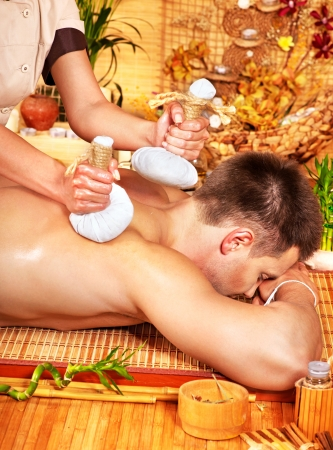 Man getting herbal ball massage treatments  in spa. Stock Photo - 16084398