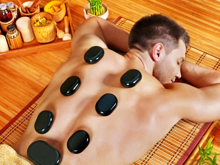 male massage: Man getting stone therapy massage in bamboo spa.
