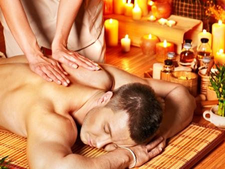 oil massage: Man getting aroma massage in bamboo spa. Stock Photo