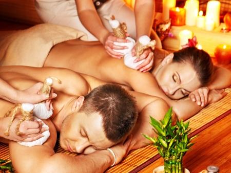 massage: L'homme et la femme se massage � base de plantes balle dans le spa de bambou. Banque d'images
