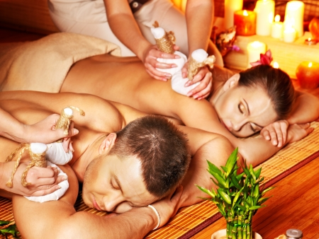 day spa: Man and woman getting herbal ball massage in bamboo spa.