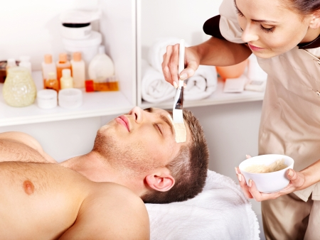 male facial: Man with clay facial mask in beauty spa.