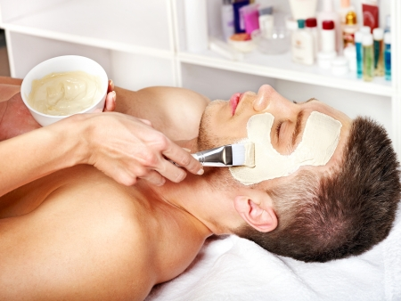 tratamiento facial: Hombre con m�scara facial de barro en el spa de belleza.