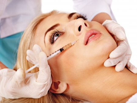 Doctor woman giving botox injections. Isolated. photo