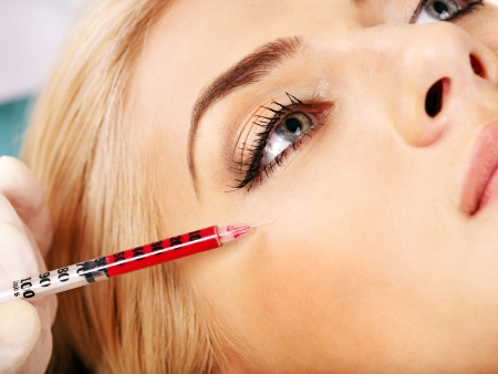 injection: Beauty woman giving botox injections. Stock Photo