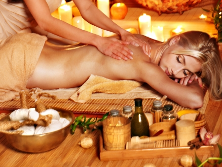 pressure massage: Blond woman getting herbal ball massage in spa.