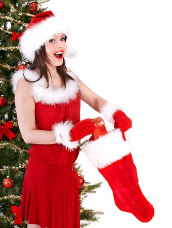 Girl in Santa hat holding christmas socks and gift box by christmas tree.  Isolated. Stock Photo - 16084482