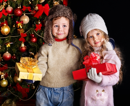 mitten: Children with gift box near Christmas tree. Outdoor.