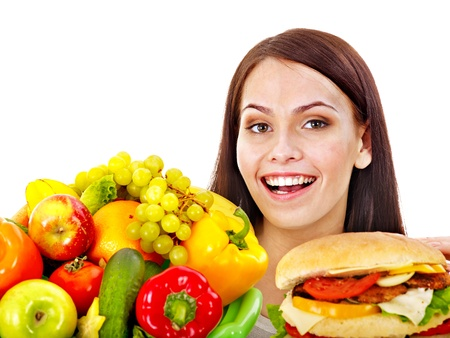 Woman choosing between fruit and hamburger. Isolated. Stock Photo - 16084422
