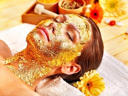 tratamiento facial: Mujer que consigue la máscara facial de oro. Foto de archivo