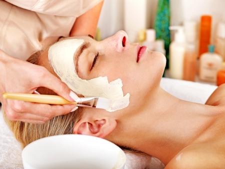 tratamiento facial: Mujer con máscara facial de barro en el spa de belleza. Foto de archivo
