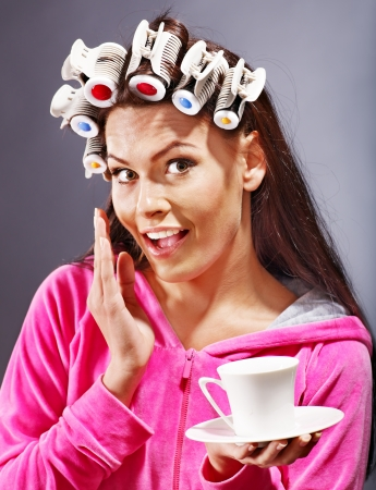 hot rollers: Woman wear hair curlers on head holding cup of coffee. Stock Photo