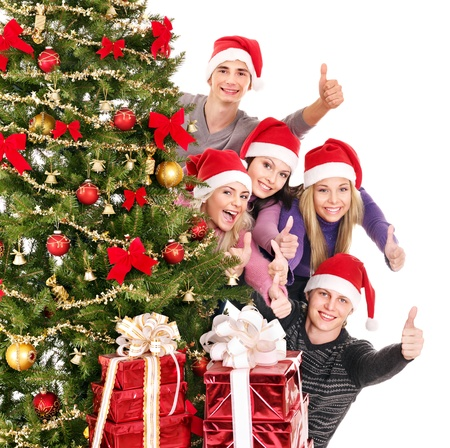 christmas funny: Group young people in Santa hat showing thumb up by Christmas tree..