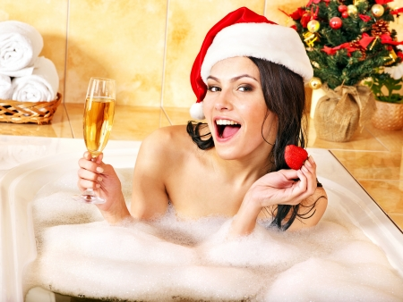 soap sud: Woman in santa hat relax in bath. Christmas concept.