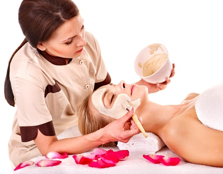 cosmetician: Woman with clay facial mask in beauty spa. Isolated. Stock Photo