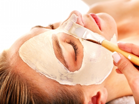 health resort treatment: Woman with clay facial mask in beauty spa. Isolated. Stock Photo
