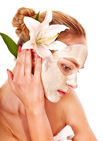 Woman  with facial mask  holding flower. Isolated. photo