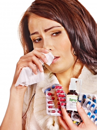 cold remedy: Young woman with handkerchief having  tablets and pills.  Isolated. Stock Photo