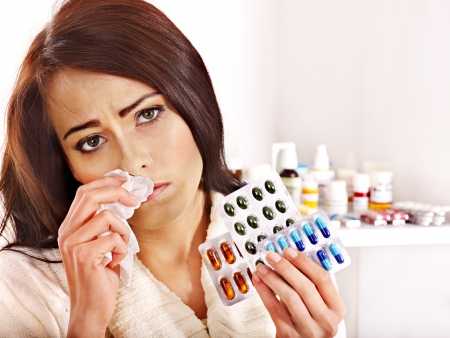 Young woman with handkerchief having  tablets and pills.  Indoors. Stock Photo - 16222063