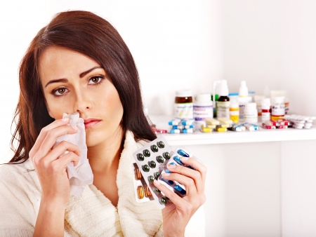 woman sweater: Young woman with handkerchief having  tablets and pills.  Indoors. Stock Photo