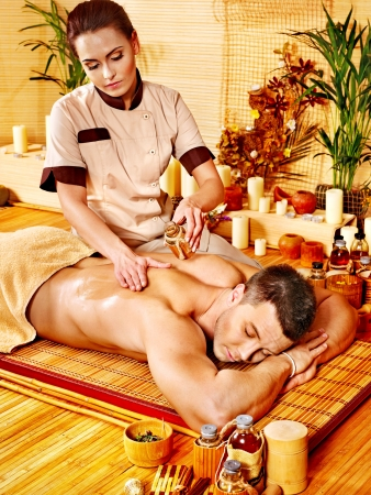 body conscious: Man getting massage in bamboo spa. Female therapist.