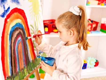 children painting: Child drawing on the easel at school.