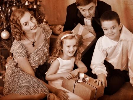 ni�os vistiendose: Familia feliz con los ni�os que recibieron los regalos bajo el �rbol de Navidad. En blanco y negro retro.
