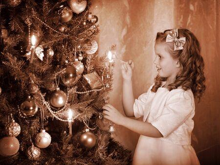 ni�os vistiendose: Peque�as luces chica velas en el �rbol de Navidad. Negro y blanco retro.