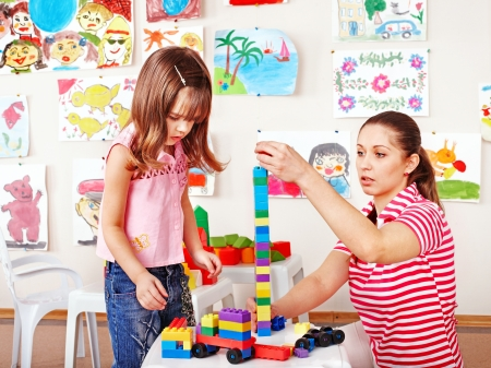 daycare: Little girl  playing construction set with mother.