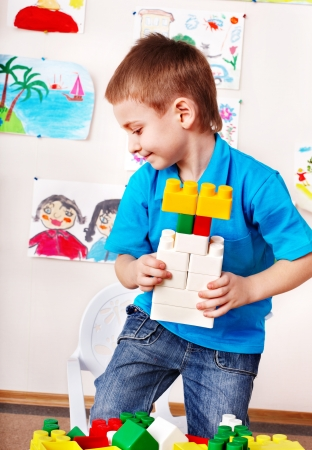 nurser: Little boy playing construction set.