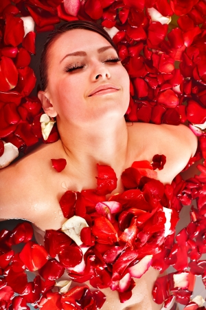 Beautiful young woman in rose petal swim water. Beauty spa. photo