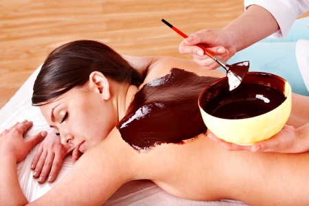 health resort treatment: Beautiful girl having chocolate facial mask apply by beautician.