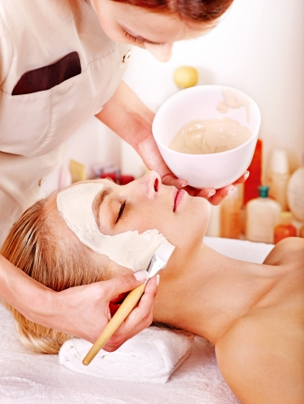 cosmetician: Woman with clay facial mask in beauty spa. Stock Photo