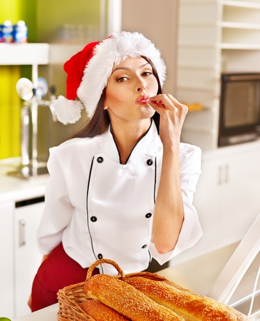 Female chef in Santa hat baking baguette bread. photo
