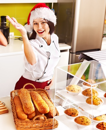 Female chef in Santa hat baking baguette bread. photo
