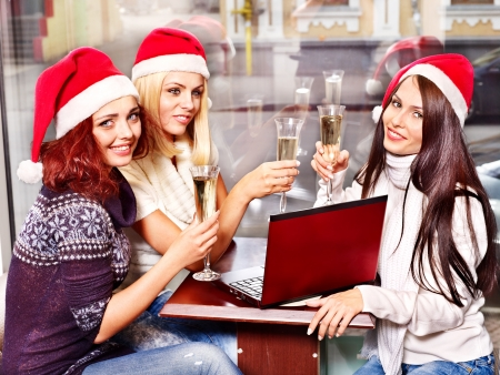 Women in santa hat drinking champagne in cafeteria. photo