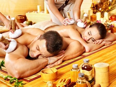 massage homme: L'homme et la femme se massage à base de plantes balle dans le spa de bambou. Banque d'images