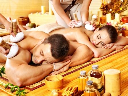 massage oil: L'homme et la femme se massage � base de plantes balle dans le spa de bambou. Banque d'images