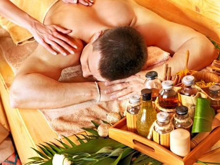 oil massage: L'homme se massage dans le spa de bambou. Th�rapeute.