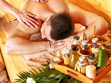 oil massage: Man getting massage in bamboo spa. Female therapist.