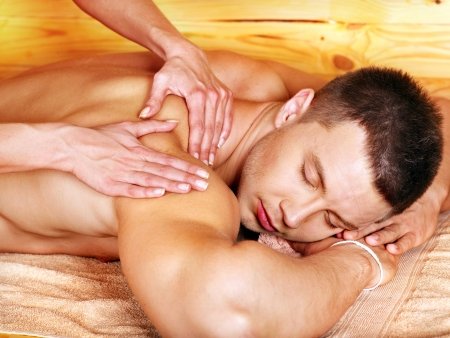 female therapist: Man getting massage in woden spa. Female therapist.