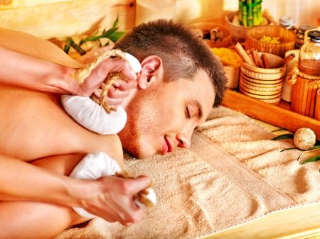Man getting herbal ball massage treatments  in spa. Stock Photo - 16637477