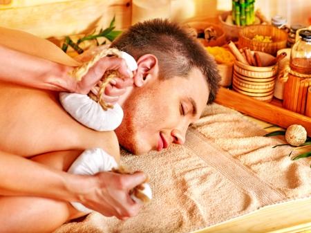 herbal massage ball: Man getting herbal ball massage treatments  in spa.