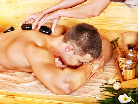 lastone therapy: Man getting stone therapy massage in bamboo spa.