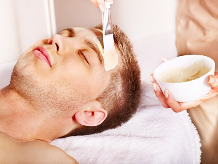 tratamiento facial: Hombre con máscara facial de barro en el spa de belleza.
