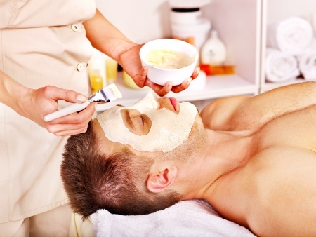 Man with clay facial mask in beauty spa. photo