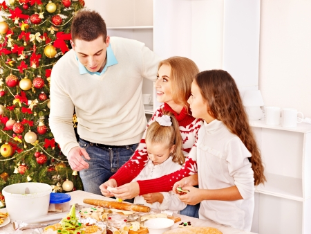 christmas cooking: Happy family with children rolling dough in Christmas kitchen.