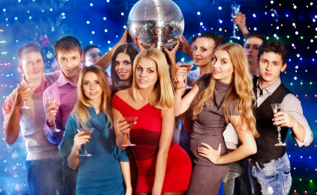 Group people with  champagne dancing at party. Disco ball. photo