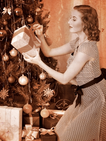 retro styled: Woman receiving gifts under Christmas tree. Black and white retro.