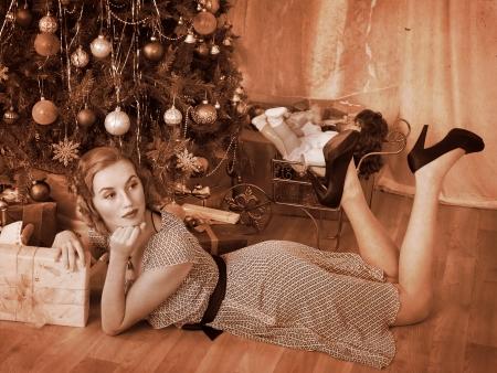 vistiendose: Mujer que recibe los regalos bajo el árbol de Navidad. En blanco y negro retro.